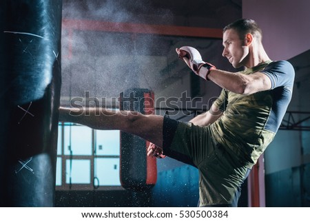 The young man workout a kick on the punching bag in gym. Royalty-Free Stock Photo #530500384