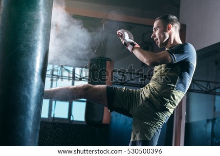 The young man workout a kick on the punching bag in gym. Royalty-Free Stock Photo #530500396