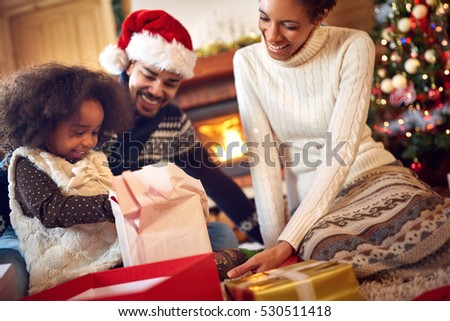 Cheerful black family together spend Christmas time in wooden house
