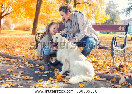 Family,woman and her daughter walk with his dog, autumn park.Colored photo
