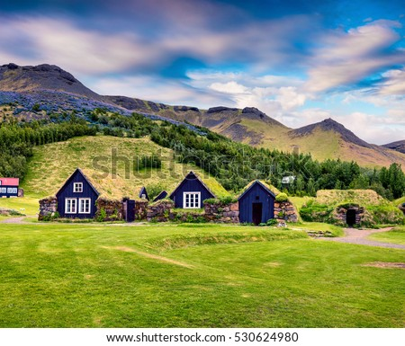 Typical view of Icelandic turf-top houses. Colorful summer morning in the Skogar village, south Iceland, Europe. Artistic style post processed photo. #530624980