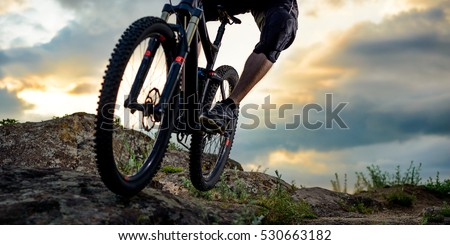 Cyclist Riding the Bike Down Rocky Hill at Sunset. Close up Extreme Sport Concept. Space for Text. Royalty-Free Stock Photo #530663182