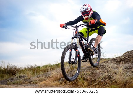 Professional Cyclist Riding the Bike Down Rocky Hill. Extreme Sport Concept. Space for Text. #530663236