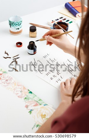 Girl writing calligraphy on postcards. Art design. #530698579