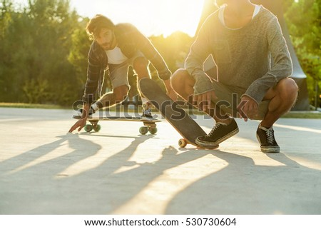 Skater friends performing with longboards in city urban park with back light- Young people having fun training skateboard extreme sport - Focus on right man feet - Warm filter with original sunlight #530730604