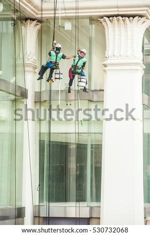 BANGKOK, THAILAND-NOVEMBER 18,2016 :Group of unidentified Glass cleaner abseiling from a tall building. Window cleaners at work on skyscraper, Bangkok , Middle of Thailand. #530732068