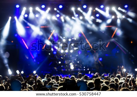silhouettes of concert crowd in front of bright stage lights. motion image #530758447