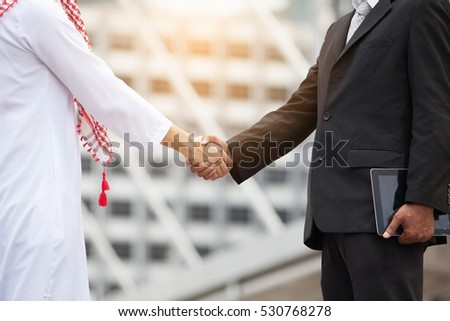 Arab Businessmen's Handshake Partnered with American Businessman Descent. Confirmation of Business alliance Partners as WELL. Adhering Respect, Commitment and Integrity in Business Partnership Deal   #530768278