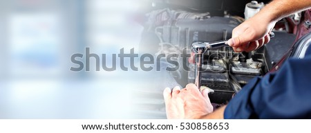 Hands of car mechanic in auto repair service. Royalty-Free Stock Photo #530858653