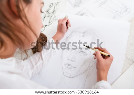 Artist drawing pencil portrait close-up. Woman painter creating picture of woman on big whatman. Art, talent, craft, hobby, occupation concept #530918164