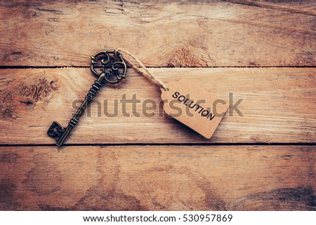 Business concept - Old key vintage on wood with tag Solution.