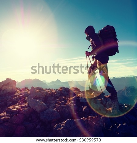Lens flare light, strong defect. Silhouette of man with hood, backpack and poles in hand. Man walk on rocky peak of mountain. Sunny day rocky mountains. #530959570