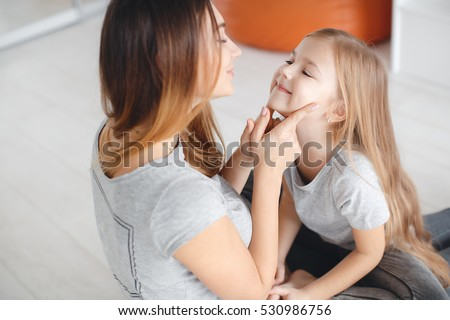 Mother with daughter having fun in living room at home. Woman and young girl playing at home smiling, hugging. happy family concept.  #530986756