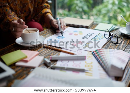 Female designer drinking coffee and working on logo