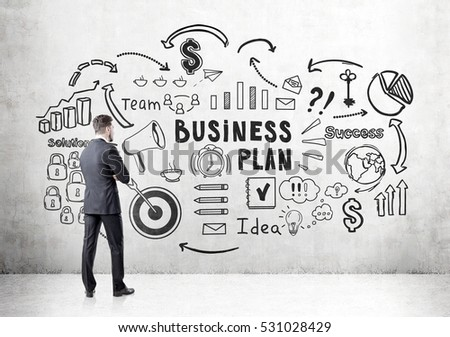 Rear view of a bearded businessman looking at a business plan sketch depicted at a concrete wall. Concept of strategy development