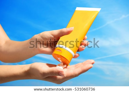 Female hands with sun protection cream on sky background. Skin care concept. #531060736