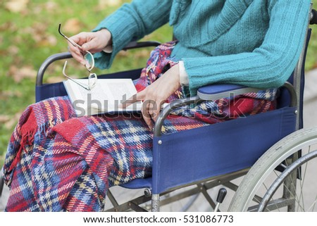 Woman in wheelchair reading a book in the park #531086773