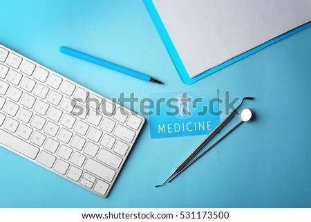 Business card, clipboard, keyboard and dental tools on blue background. Medical service concept