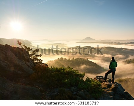 Man silhouette stay on sharp rock peak. Satisfy hiker enjoy view. Tall man on rocky cliff watching down to landscape. Vivid and strong vignetting effect. #531185719