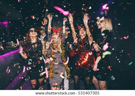 Group of friends at club having fun. New year's party Royalty-Free Stock Photo #531407305