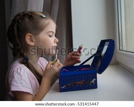 little cute girl doing make-up, nail  paint, lipstick #531415447