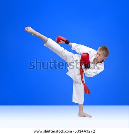 Boy is training kick leg on a blue background #531443272