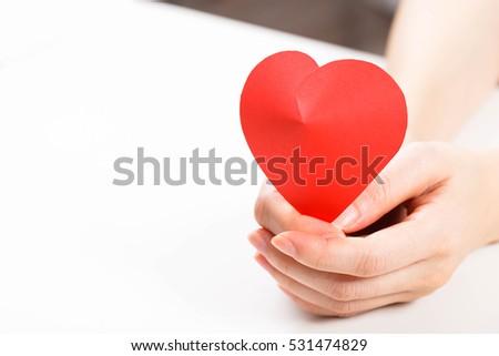 Red heart origami in girl hands. #531474829