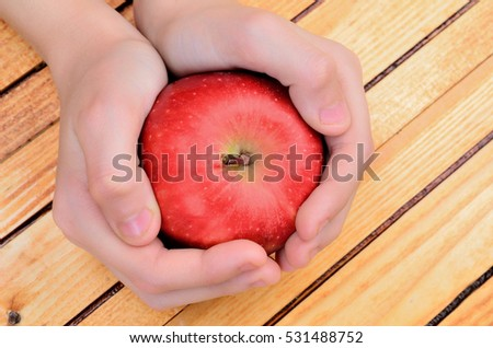 hand hold apple on wooden table #531488752