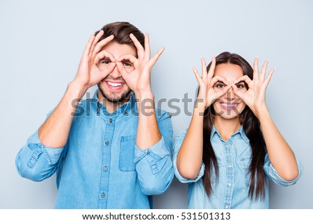 Portrait of two happy funny lovers holding fingers near eyes.