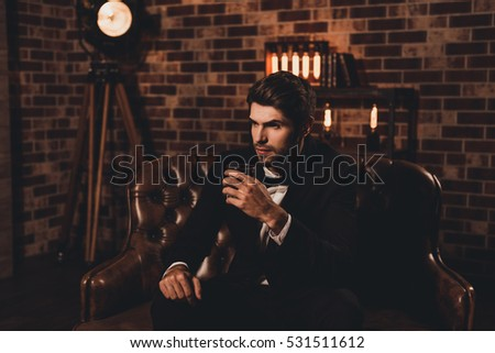 Handsome young man in elegant suit with glass of whiskey relaxing on sofa #531511612