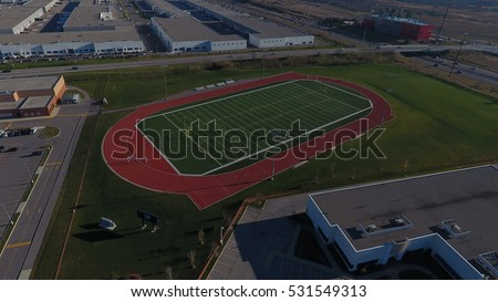 Football field with a surrounding track, shot from above with a drone  #531549313