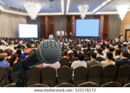 Microphone over the Abstract blurred photo of conference hall or seminar room with attendee background, Business meeting concept #531578572
