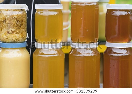 Stack of glass jars with yellow honey #531599299