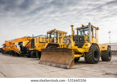Two heavy wheeled tractor one excavator and other construction machinery Royalty-Free Stock Photo #531660106