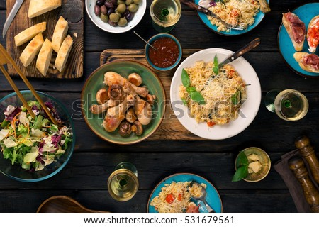 Italian risotto with cherry tomatoes, basil and parmesan cheese, roasted chicken legs, snacks and wine on dark wooden table. Italian food table, top view #531679561