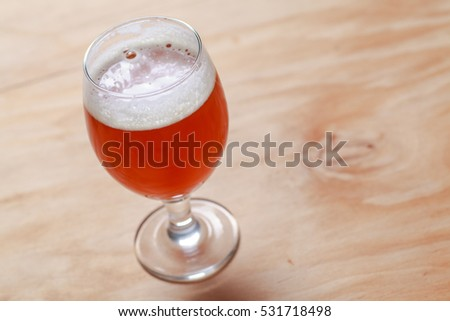 Glass of amber beer on a textured wooden surface #531718498