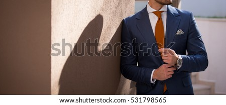 Male model in a suit posing outdoors #531798565