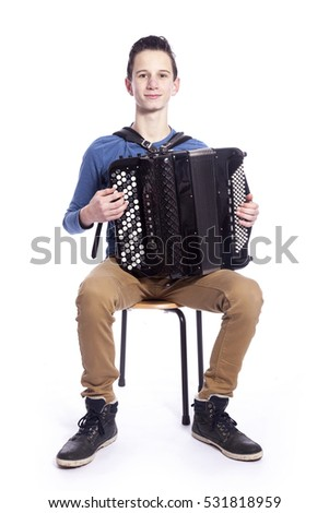 teenage caucasian boy plays the accordion in studio with white background #531818959