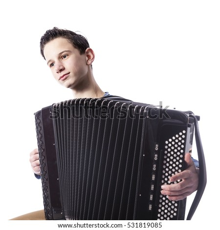 teenage caucasian boy plays the accordion in studio with white background #531819085