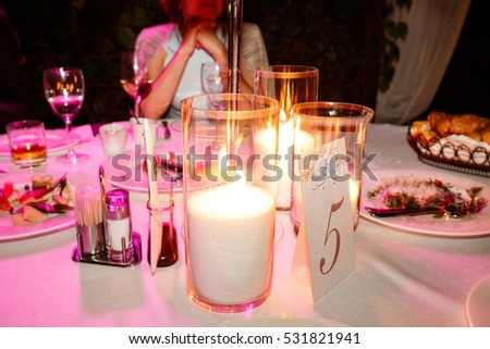 Blurred picture of card with number 5 standing before vases with burning candles