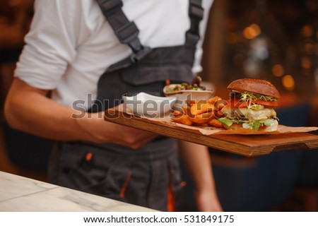 Burger with fries on waiters hands #531849175