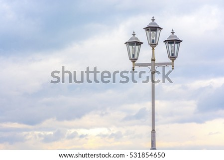 Old street lamp on a background of cloudy sky. Soft colors. Beautiful background. #531854650