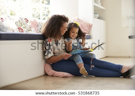 Mother sitting on the floor reading a book with her daughter #531868735