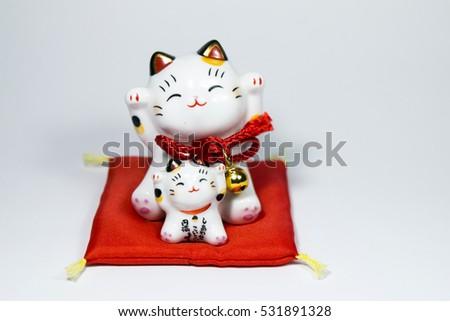 Beckoning cat also known as maneki neko isolated on white #531891328
