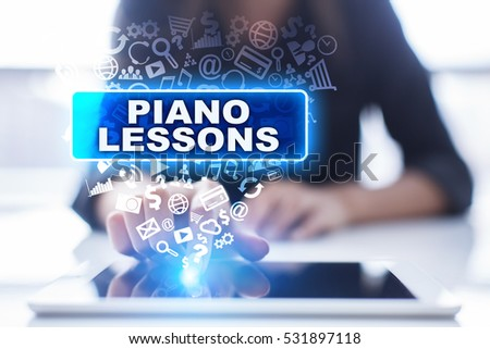Woman is using tablet pc, pressing on virtual screen and selecting piano lessons. #531897118