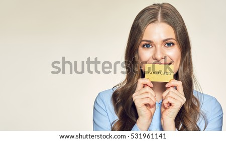 Smiling young woman holding gold credit card. isolated portrait. #531961141