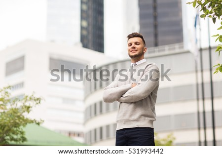 business and people concept - happy smiling young man on city street #531993442