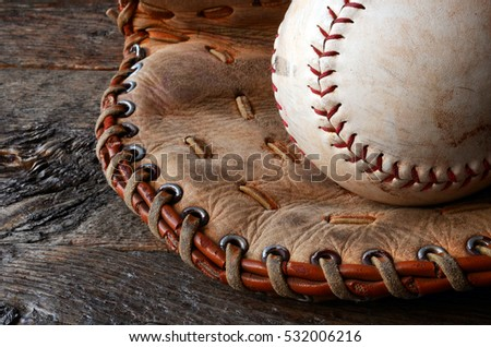 A low angle image of an old used baseball and leather baseball glove. Royalty-Free Stock Photo #532006216
