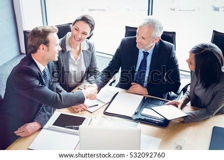 High angle view of businessmen shaking hands in conference room at office Royalty-Free Stock Photo #532092760