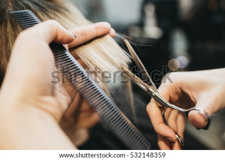 Scissors cut the girls hair Royalty-Free Stock Photo #532148359